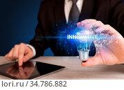 Businessman holding light bulb with INNOVATIVE inscription, innovative... Стоковое фото, фотограф Zoonar.com/ranczandras / easy Fotostock / Фотобанк Лори