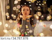 woman blowing confetti from her hands at night. Стоковое фото, фотограф Syda Productions / Фотобанк Лори