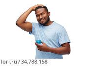 african american man applying hair styling wax. Стоковое фото, фотограф Syda Productions / Фотобанк Лори