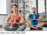 happy couple meditating in yoga lotus pose at home. Стоковое фото, фотограф Syda Productions / Фотобанк Лори
