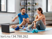 happy couple with laptop doing sports at home. Стоковое фото, фотограф Syda Productions / Фотобанк Лори