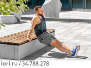 young man doing triceps dip on city street. Стоковое фото, фотограф Syda Productions / Фотобанк Лори