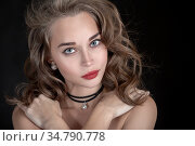 Luxury serious woman with curly long hair on black background. Стоковое фото, фотограф Zoonar.com/A.Tugolukov / easy Fotostock / Фотобанк Лори