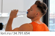 Fit and handsome young man drinking water from plastic bottle, at home. Стоковое фото, фотограф Zoonar.com/Stefano Cavoretto / easy Fotostock / Фотобанк Лори