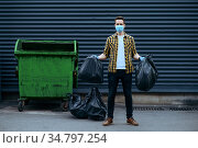 Volunteer in mask holds plastic trash bags. Стоковое фото, фотограф Tryapitsyn Sergiy / Фотобанк Лори