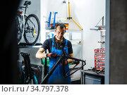 Bicycle repair in workshop, man fixing crank. Стоковое фото, фотограф Tryapitsyn Sergiy / Фотобанк Лори