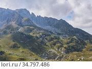 Mountainside with green ledges, and above it an impregnable rocky peak. Стоковое фото, фотограф Евгений Харитонов / Фотобанк Лори