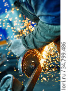 Cutting a metal beam using an angle grinder. A lot of sparks fly out from under the disk. Стоковое фото, фотограф Андрей Радченко / Фотобанк Лори
