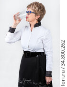 Senior Caucasian woman drinking fresh water from glass, studio with a grey background, side view. Стоковое фото, фотограф Кекяляйнен Андрей / Фотобанк Лори