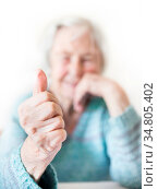Content 96 years old elderly woman giving a thumb up and looking at... Стоковое фото, фотограф Zoonar.com/Matej Kastelic / easy Fotostock / Фотобанк Лори