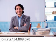 Young handsome teacher in front of whiteboard. Стоковое фото, фотограф Zoonar.com/Elnur Amikishiyev / easy Fotostock / Фотобанк Лори