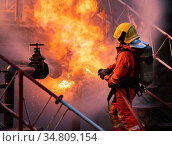 Firefighter using water fog type fire extinguisher to fighting with... Стоковое фото, фотограф Vichaya Kiatying-Angsulee / easy Fotostock / Фотобанк Лори