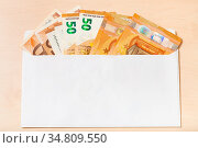 Fan from several fifty euro notes in open mail envelope on wooden... Стоковое фото, фотограф Zoonar.com/Valery Voennyy / easy Fotostock / Фотобанк Лори