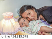 Lovely face of a happy woman embracing her young daughter in the bed. Стоковое фото, фотограф Giovanni Gagliardi / easy Fotostock / Фотобанк Лори