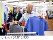 mature european man chooses tee shirt in clothing department of supermarket. Стоковое фото, фотограф Татьяна Яцевич / Фотобанк Лори