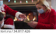 Santa Claus wearing face mask giving the gift box to mother and daughter. Стоковое видео, агентство Wavebreak Media / Фотобанк Лори
