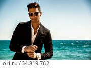 Young handsome man in classical suit on beach holding sunglasses while... Стоковое фото, фотограф Zoonar.com/STEFANO CAVORETTO / easy Fotostock / Фотобанк Лори