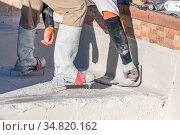 Worker Wearing Spiked Shoes Smoothing Wet Pool Plaster With Trowel. Стоковое фото, фотограф Zoonar.com/Andy Dean Photography / easy Fotostock / Фотобанк Лори