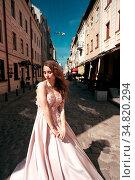 Young beautiful woman model in a stylish evening dress posing on a... Стоковое фото, фотограф Zoonar.com/Oleksii Hrecheniuk / easy Fotostock / Фотобанк Лори