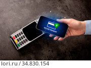 Hand paying on terminal with smartphone in secure payment system. Стоковое фото, фотограф Zoonar.com/rancz / easy Fotostock / Фотобанк Лори