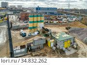 A concrete mixer truck transports concrete through a construction site. Стоковое фото, фотограф Андрей Радченко / Фотобанк Лори