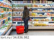 Женщина с корзиной в молочном отделе супермаркета Billa в день открытия (2018 год). Редакционное фото, фотограф Сайганов Александр / Фотобанк Лори