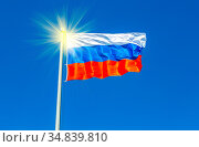 National flag of Russia waving in the wind against the blue sky. Стоковое фото, фотограф Zoonar.com/Alexander Blinov / easy Fotostock / Фотобанк Лори