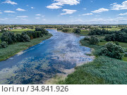 A small river flowing through meadows and agricultural fields. Aerial view. Evening shot with the setting sun. Стоковое фото, фотограф Андрей Радченко / Фотобанк Лори