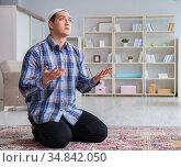 Young muslim man praying at home (2017 год). Стоковое фото, фотограф Elnur / Фотобанк Лори