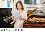 Pretty saleswoman in piano record store. Стоковое фото, фотограф Яков Филимонов / Фотобанк Лори