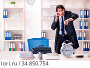 The young male employee in the office in time management concept. Стоковое фото, фотограф Zoonar.com/Elnur Amikishiyev / easy Fotostock / Фотобанк Лори