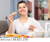Attractive woman with tea eating croissant at table while breakfast. Стоковое фото, фотограф Яков Филимонов / Фотобанк Лори