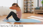 smiling young woman exercising at home. Стоковое видео, видеограф Syda Productions / Фотобанк Лори