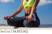 young woman meditating in lotus pose at seaside. Стоковое видео, видеограф Syda Productions / Фотобанк Лори
