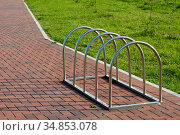 Modern Parking for bicycles made of stainless steel on the background of paving slabs. Стоковое фото, фотограф Сергей Трофименко / Фотобанк Лори