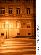 """A lamp near pedestrian crossing on a deserted night street in Prague. Inscriptions: """"Konvitska street, district Staroe Mesto, Prague 1"""" and """"Parking is reserved from 08-06 hours for areas of the city"""" (2017 год). Стоковое фото, фотограф Сергей Фролов / Фотобанк Лори"""