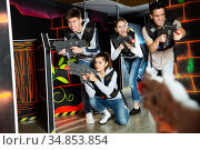 Excited young people playing enthusiastically laser tag game two teams opposite each other in dark room. Стоковое фото, фотограф Яков Филимонов / Фотобанк Лори