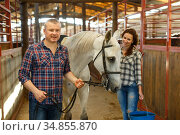 Couple with bucket before cleaning horse while standing at stabling. Стоковое фото, фотограф Яков Филимонов / Фотобанк Лори