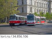 Два городских трамвая в повороте солнечным апрельским днем. Брно, Чехия (2018 год). Редакционное фото, фотограф Виктор Карасев / Фотобанк Лори