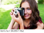happy woman with camera photographing at park. Стоковое фото, фотограф Syda Productions / Фотобанк Лори