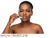 african american woman applying lipstick. Стоковое фото, фотограф Syda Productions / Фотобанк Лори
