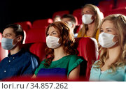 people in masks watching movie in theater. Стоковое фото, фотограф Syda Productions / Фотобанк Лори