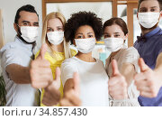 people in masks showing thumbs up at office. Стоковое фото, фотограф Syda Productions / Фотобанк Лори