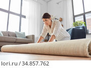 young woman unfolding carpet at home. Стоковое фото, фотограф Syda Productions / Фотобанк Лори