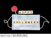 Striped colorful lollipop, medical mask and wooden words Happy Halloween on black. Halloween background decor holiday concept. Стоковое фото, фотограф Papoyan Irina / Фотобанк Лори