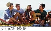 Man playing guitar for friends sitting on the beach 4k. Стоковое видео, агентство Wavebreak Media / Фотобанк Лори