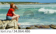 Woman sitting on a rock and looking at the ocean waves 4k. Стоковое видео, агентство Wavebreak Media / Фотобанк Лори