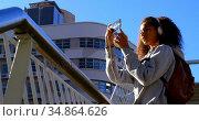 Female model taking photos with mobile phone in the city 4k. Стоковое видео, агентство Wavebreak Media / Фотобанк Лори