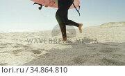 Surfer with surfboard running on the beach 4K 4k. Стоковое видео, агентство Wavebreak Media / Фотобанк Лори