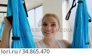 Woman sitting on hammock swing at fitness studio 4k. Стоковое видео, агентство Wavebreak Media / Фотобанк Лори